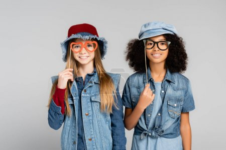 smiling multicultural girls in denim clothes holding party spectacles isolated on grey