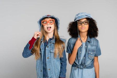 Photo pour Fille à la mode qui sort la langue tout en tenant des lunettes de vue coupées en papier avec un ami afro-américain sur gris - image libre de droit