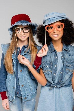 Photo pour Élégant interracial filles avec papier découpé lunettes souriant à la caméra isolé sur gris - image libre de droit