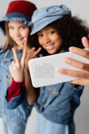 Photo pour Heureux interracial filles montrant la victoire et le rock signes tout en prenant selfie sur gris, fond flou - image libre de droit