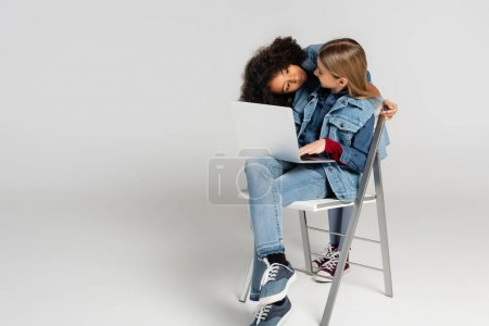 Photo for African american girl looking at trendy friend sitting on chair with laptop on grey - Royalty Free Image