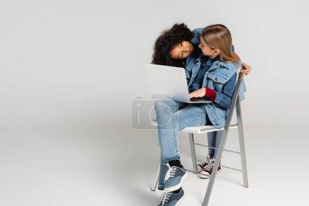 Photo pour Afro-américaine fille à la recherche à la mode ami assis sur chaise avec ordinateur portable sur gris - image libre de droit