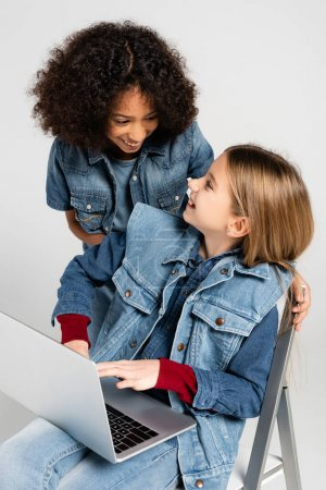 Photo for Cheerful african american girl in denim clothes near happy friend sitting on chair with laptop isolated on grey - Royalty Free Image