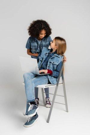 Photo pour Joyeuse fille afro-américaine regardant heureux ami élégant assis sur une chaise avec ordinateur portable sur gris - image libre de droit