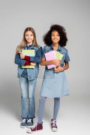 Photo pour Vue pleine longueur des amis interracial à la mode souriant tout en se tenant debout avec des livres sur le gris - image libre de droit