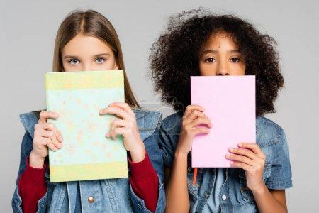 Photo pour Tendance interracial écolières regarder caméra tout en tenant des livres isolés sur gris - image libre de droit