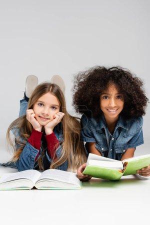 Photo pour Heureux écoliers multiculturels souriant à la caméra tout en étant couché avec des livres sur gris - image libre de droit