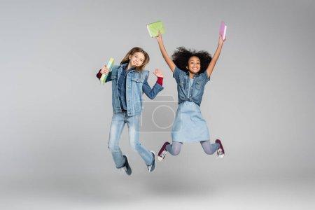 Photo pour Excité écolières multiculturelles en denim vêtements lévitation avec des manuels sur gris - image libre de droit