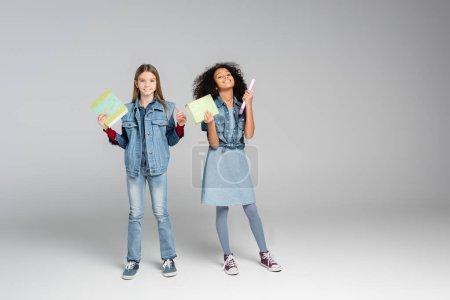 Photo pour Vue pleine longueur des écolières multiculturelles à la mode debout avec des livres sur le gris - image libre de droit