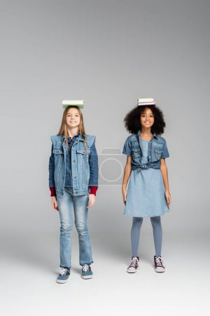 Photo pour Vue pleine longueur des écolières interracial à la mode debout avec des livres sur les têtes sur gris - image libre de droit