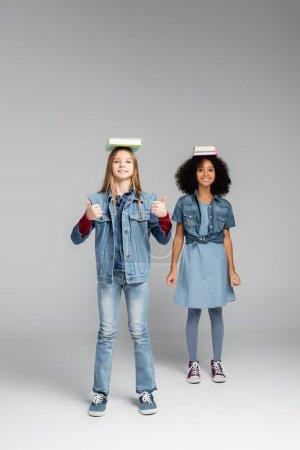 Photo pour Souriant interracial écolières en denim vêtements et gommes debout avec des livres sur les têtes sur gris - image libre de droit