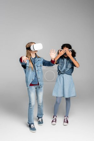 Photo for African american girl covering vr headset while standing near friend on grey - Royalty Free Image