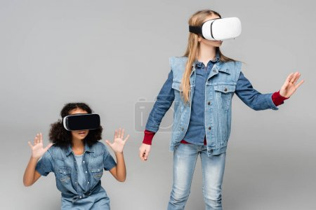 Photo for Stylish multicultural friends gesturing in vr headsets on grey - Royalty Free Image
