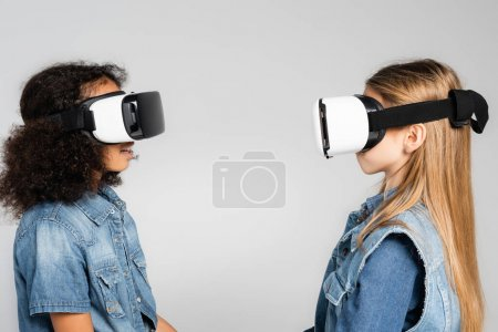 Photo for Side view of fashionable interracial kids in vr headsets looking at each other isolated on grey - Royalty Free Image