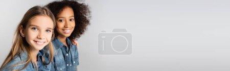 Photo pour Deux filles interraciales heureuses en denim souriant à la caméra isolée sur gris, bannière - image libre de droit