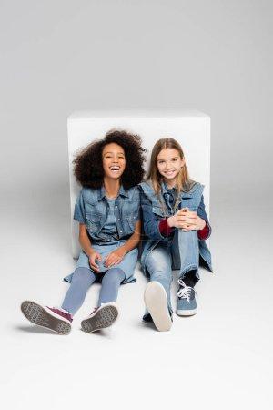 excited interracial children in denim clothes sitting near white box on grey