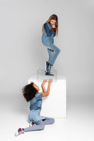 cheerful girl standing on white cube while african american girl sitting on grey