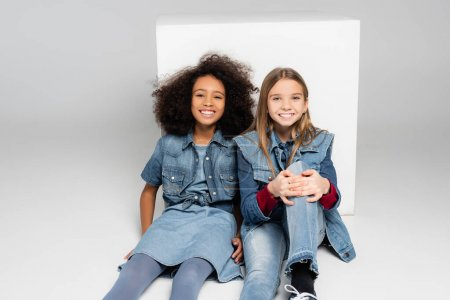 trendy interracial girls smiling at camera while sitting near white box on grey