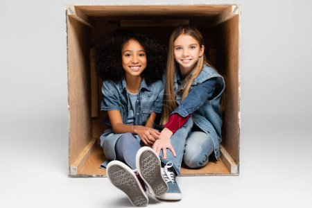 Photo for Cheerful multicultural girls in denim clothes sitting in wooden box on grey - Royalty Free Image