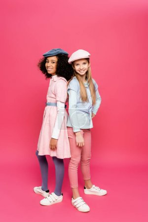 Photo pour Vue pleine longueur de filles multiculturelles gaies en vêtements à la mode et casquettes regardant la caméra sur rose - image libre de droit