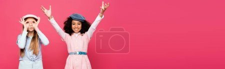 Photo for Excited interracial girls in trendy clothes and caps posing isolated on pink, banner - Royalty Free Image