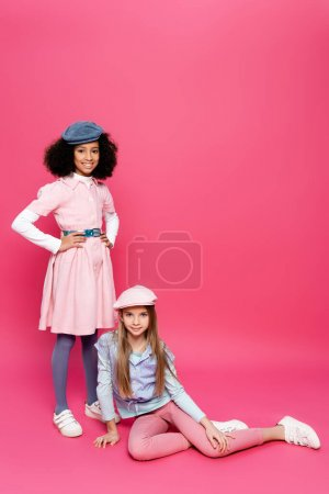 Photo pour Heureux afro-américain fille posant avec les mains sur les hanches près ami assis sur rose - image libre de droit