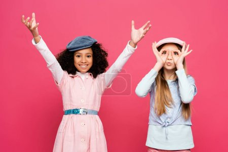 trendy girl imitating eyeglasses near cheerful african american girl with raised hands isolated on pink