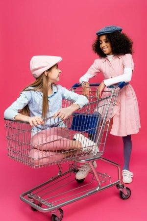 Photo pour Mode interracial filles regarder l'autre tout en s'amusant avec panier sur rose - image libre de droit