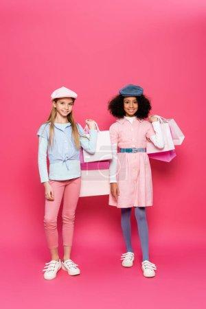 Photo pour Vue pleine longueur des enfants interracial en tenue de printemps à la mode posant avec des sacs à provisions sur rose - image libre de droit