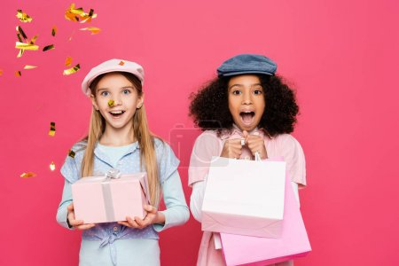 Photo for Excited multicultural kids in trendy clothes posing with presents isolated on pink - Royalty Free Image