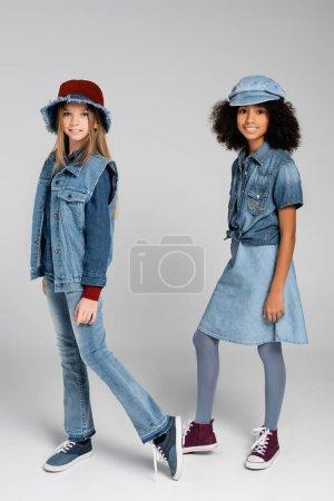 Photo pour Deux filles interracial en denim à la mode vêtements et chapeaux posant sur gris - image libre de droit