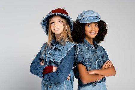 Photo pour Joyeux, branché interracial filles souriant à la caméra tout en se tenant avec les bras croisés sur gris - image libre de droit