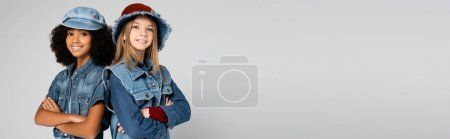 happy interracial girls in denim clothes and hats posing with crossed arms isolated on grey, banner