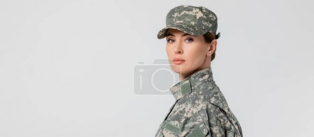 Photo for Military woman looking at camera isolated on grey, banner - Royalty Free Image