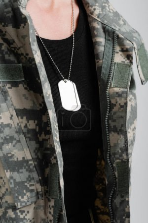 Cropped view of military dog tags on necklace of soldier isolated on grey