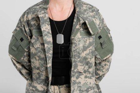 Photo pour Vue recadrée des étiquettes de chien sur le collier de la femme militaire isolée sur gris - image libre de droit
