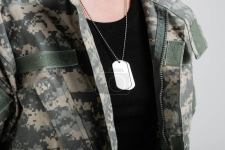 Cropped view of silver dog tags on neck of woman in military uniform isolated on grey