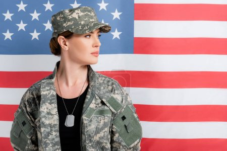 Soldier in uniform looking away near american flag at background