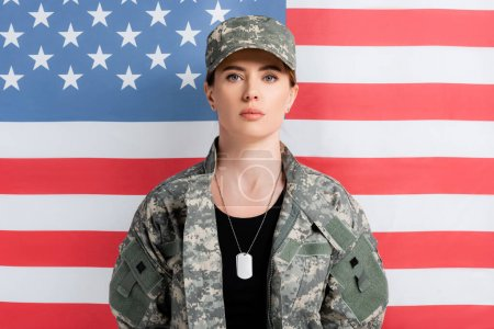 Woman in military uniform and dog tags looking at camera near american flag at background