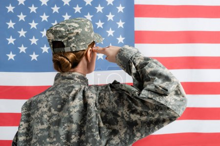 Back view of soldier saluting near american flag at background