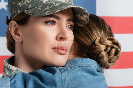 Woman in military uniform standing near daughter and american flag at background