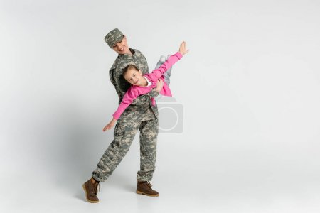 Smiling woman in camouflage holding cheerful kid on grey background