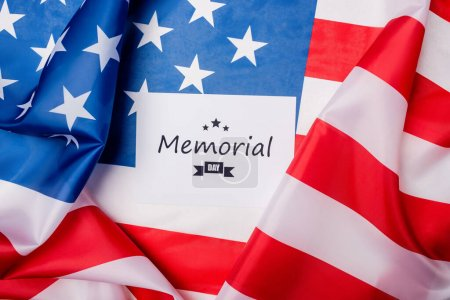 Top view of card with memorial day lettering on american flag