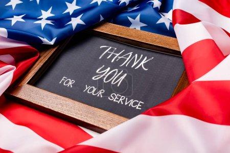 Kreidetafel mit Dankeschön für Ihren Service-Schriftzug auf amerikanischer Flagge