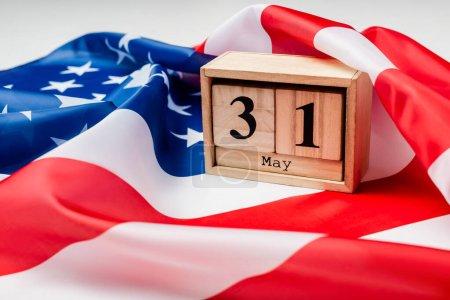Nahaufnahme des Kalenders mit 31 Mai Datum auf amerikanischer Flagge auf unscharfem Vordergrund auf grauem Hintergrund
