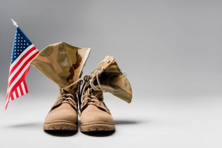 Military boots with american flag on grey background