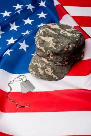 Photo pour Casquette militaire et plaques de chien sur le drapeau américain - image libre de droit