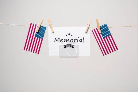 Karte mit Gedenktag-Schriftzug und amerikanischen Flaggen auf Seil isoliert auf grau