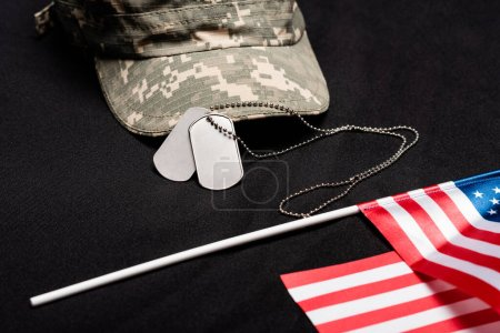 Close up view of dog tags, cap and american flag on black background