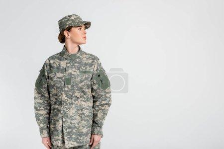 Photo pour Soldat en casquette et uniforme regardant loin isolé sur gris - image libre de droit